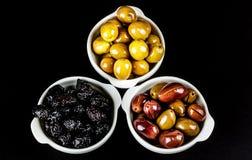 Olive nere, verdi e rosa in ciotole Fotografia Stock