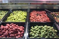 Olive nostrane quattro tipi differenti, verde chiaro, scuro, rosso, esposti al mercato per la vendita della gente avida immagine stock