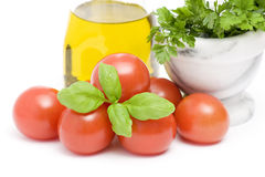 Olive oi, tomatoes, basil and parsley Stock Photos