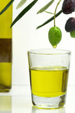 Olive oil. Olive dripping oil into glass with bottle in background Stock Photos