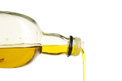 Olive oil. Pouring from a glass bottle against white Stock Photography