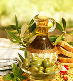 Olive oil. In bottle and fresh green olives in glass plate on the table, healthy organic nutrition, traditional lebanese cuisine, ripe fruits, food still life Royalty Free Stock Photo