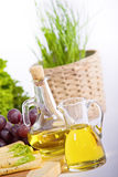Olive oil. In bottles, cheese, grape and fresh herbs royalty free stock images