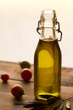 Olive oil. Inside a bottle, with some olives and tomatoes on the side Royalty Free Stock Image