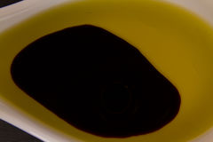 Olive oil and balsamic vinegar on ceramic spoon Royalty Free Stock Images