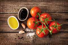 Olive oil, balsamic vinegar, garlic, salt and pepper - vinaigrette dressing. Vinaigrette or french dressing recipe ingredients and tomato branch on vintage wood royalty free stock photography