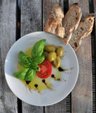 Olive oil, basil, tomato, olives and bread stock photography