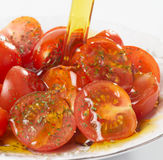 Olive oil being poured on spicy tomatos Royalty Free Stock Image