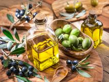 Olive oil and berries are on the olive wooden tray. stock images