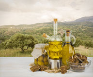 Olive oil and black bread over trees of olives background Stock Photos