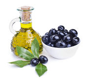 Olive oil and black olives with leaves Stock Photos