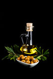 Olive oil bottle, green olives, and olive branch. Isolated on black Stock Photography