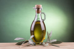 Olive oil bottle with green spotlight background royalty free stock images