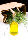 Olive oil bottle and herbs with Paper bag on white wooden  backg Royalty Free Stock Images