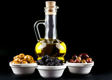 Olive oil bottle and olives in bowls on black. Royalty Free Stock Images