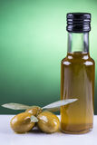 Olive oil bottle and olives on green background Stock Image