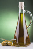 Olive oil bottle and olives on green background Royalty Free Stock Photo