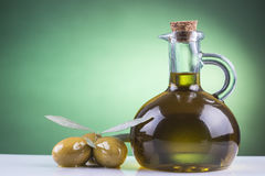 Olive oil bottle and olives on green background Stock Photos