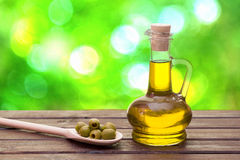 Olive oil. In bottle and olives in spoon in green bokeh background Stock Image