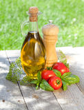 Olive oil bottle, pepper shaker, basil and ripe tomatoes. On wooden table Stock Photography