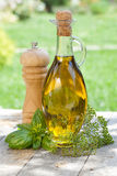 Olive oil bottle, pepper shaker and herbs Royalty Free Stock Photos