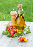 Olive oil bottle, pepper shaker, tomatoes and herbs. On wooden table Royalty Free Stock Photos