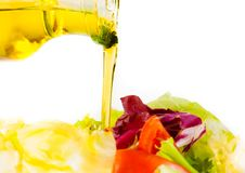 Olive oil bottle pouring in the Italian fresh salad on white Stock Photos