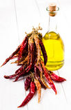 Olive oil bottle and Red hot chili pepper on white wooden backgr Royalty Free Stock Image