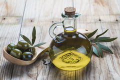 Olive oil bottle and a spoon with olives Royalty Free Stock Images