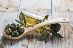 Olive oil bottle and a spoon with olives Royalty Free Stock Photography