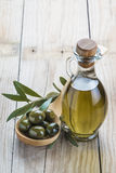 Olive oil bottle and a spoon with olives Stock Photos