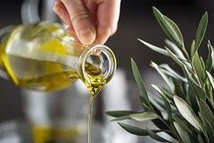 Olive oil bottle pouring close up royalty free stock photography