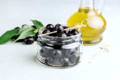 Olive oil in bottles with black olives and leaves copyspace on background Royalty Free Stock Photo