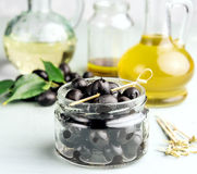 Olive oil in bottles with black olives and leaves copyspace on background Stock Images