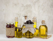 Olive oil bottles and jars with fruits on abstract background royalty free stock photography