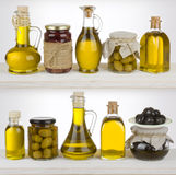 Olive oil bottles and jars standing on the shelf royalty free stock photography
