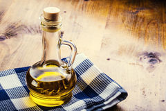 Olive oil.  Bottles of olive oil blue checkered cloth on a wooden table Stock Images