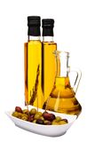 Olive oil bottles and olives. Olive oil bottles:  with rosemary, chilli pepper and bottle of pure olive oil. Bowl of mixed olives: black and green Stock Photos