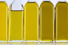 Olive Oil Bottles in a Row and Different Shades Royalty Free Stock Image