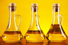 Olive oil bottles on yellow background Royalty Free Stock Image