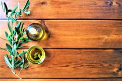 Olive oil with a branch of green olives on wooden background stock photos
