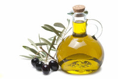 Olive oil and a branch with olives. A jar with olive oil and some black olives isolated over a white background royalty free stock photo