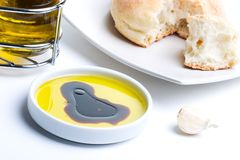 Olive oil and bread. Olive oil with balsamic vinegar, fresh bread and garlic clove over white background Stock Photos