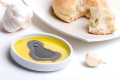 Olive oil and bread. Olive oil with balsamic vinegar, fresh bread and garlic clove over white background Royalty Free Stock Photos