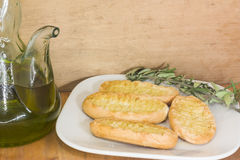 Olive Oil and bread. Jar whith olive oil, and a plate of bread with olive oil with a olive branch Stock Photos
