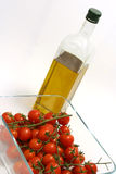 Olive oil and cherry tomatoes. Tomatoes cherry in transparent bowl with olive oil bоttle Royalty Free Stock Images