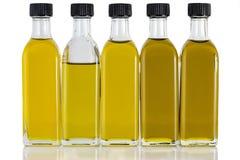 Olive Oil in cinque bottiglie e nei colori differenti Immagine Stock