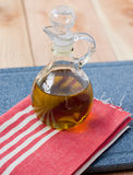 Olive oil in decanter. A jar of olive oil rests on a red striped towel on top of a cutting board in the kitchen Royalty Free Stock Photography