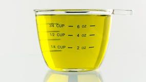 Olive Oil derramou no copo de medição de 250 ml Fotografia de Stock Royalty Free