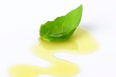 Olive oil drizzle and basil leaf Royalty Free Stock Photos